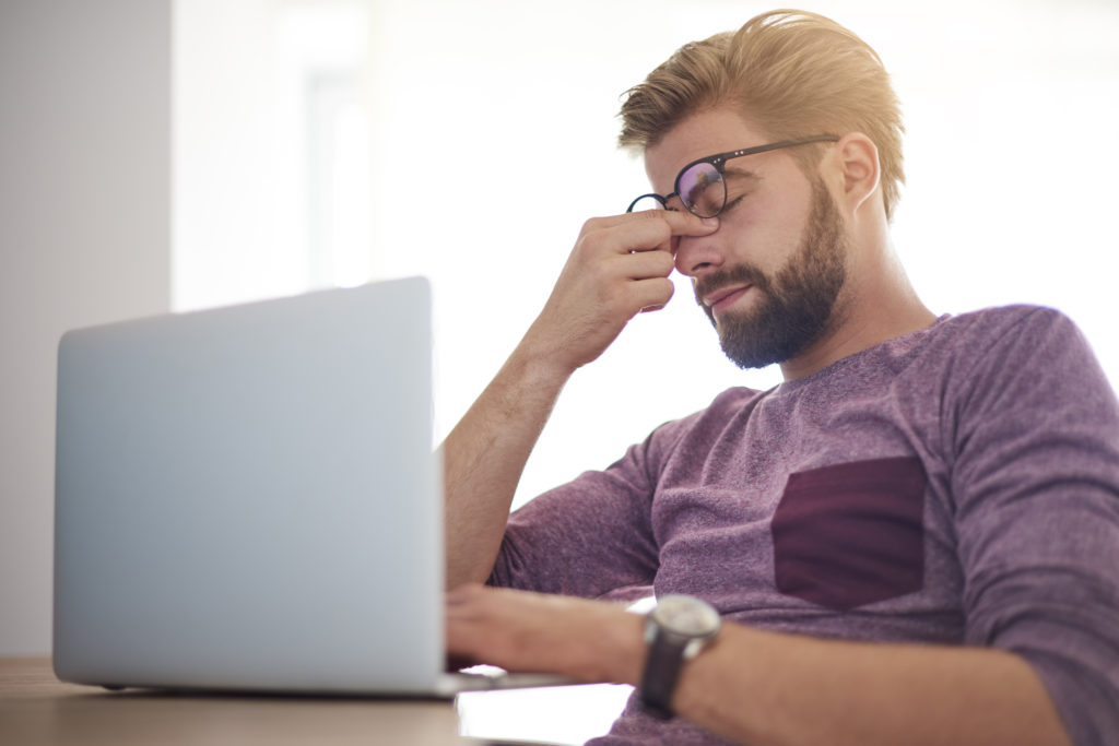 A msn wearing glasses sitting infront of a computer rubbing his eyes, he may be suffering from Dysfunctional Lens Syndrome