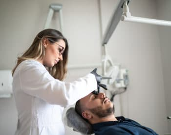 A female doctor giving a male patient botox injections in his face to prevent migraines.