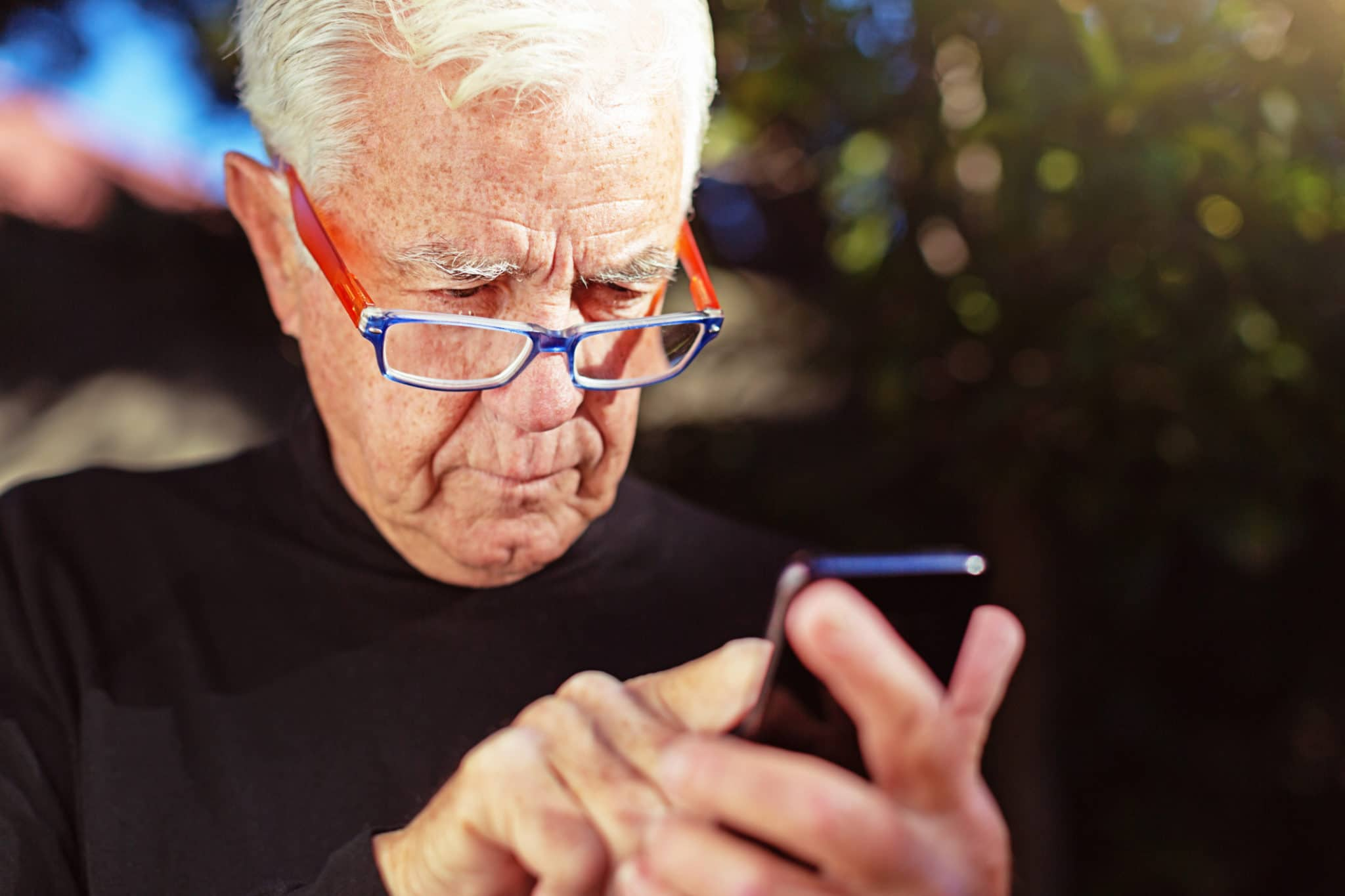 A senior man wearing eyeglasses peers down at his smart phone as he taps out a text.
