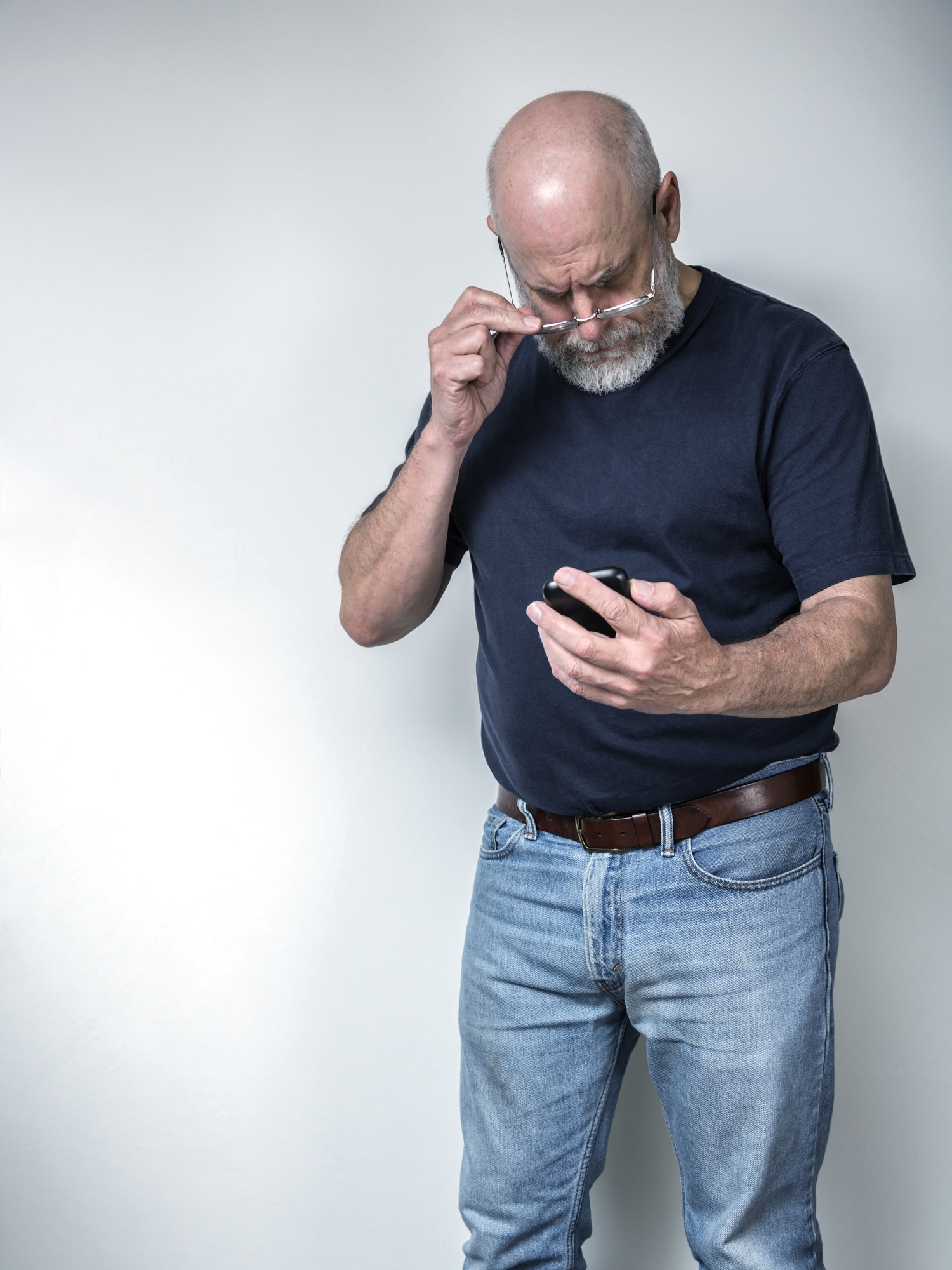 A senior adult man with poor eyesight is holding his eyeglasses away from his face as he looks down at the smartphone in his hands trying to read a text message. He is wearing a dark short sleeve t-shirt and blue jeans. He has a gray beard and mustache. Three quarter length on a grey background.