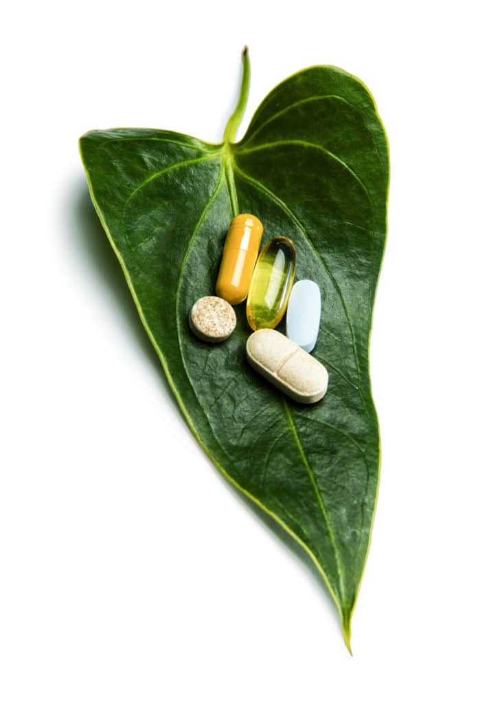This is a photograph of colorful pills on a green leaf sitting on a white background. There is a clipping path included with this file.