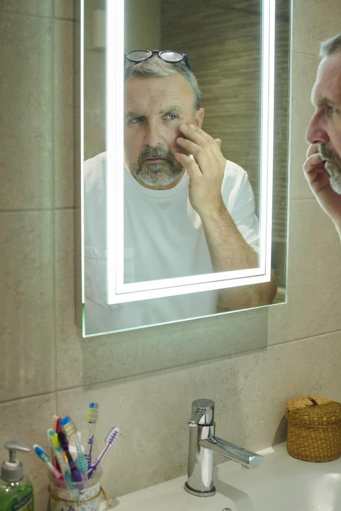 A mature man inspecting his eye in the bathroom